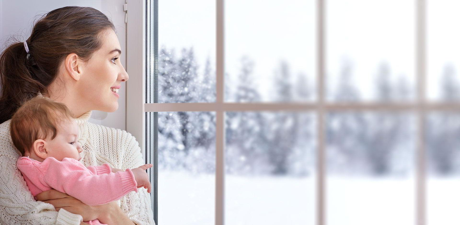 Une femme avec son bébé regarde la neige par la fenêtre