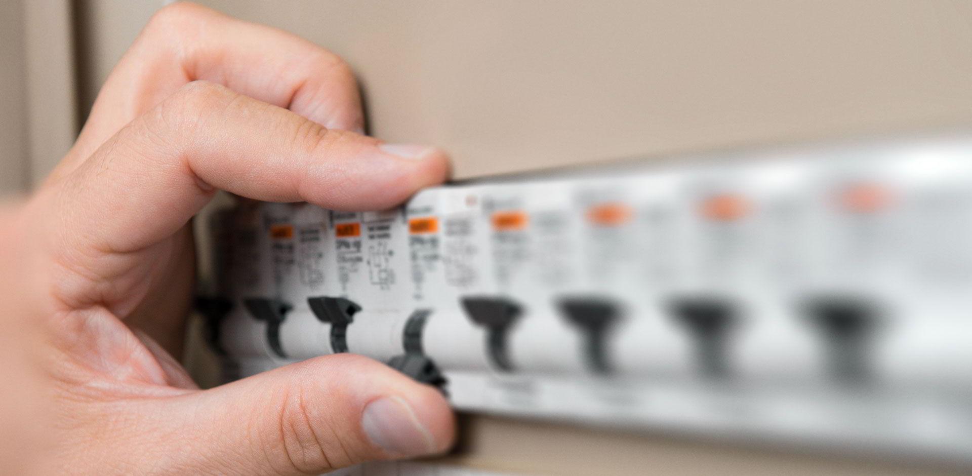 Un homme coupe son disjoncteur électrique Essensys