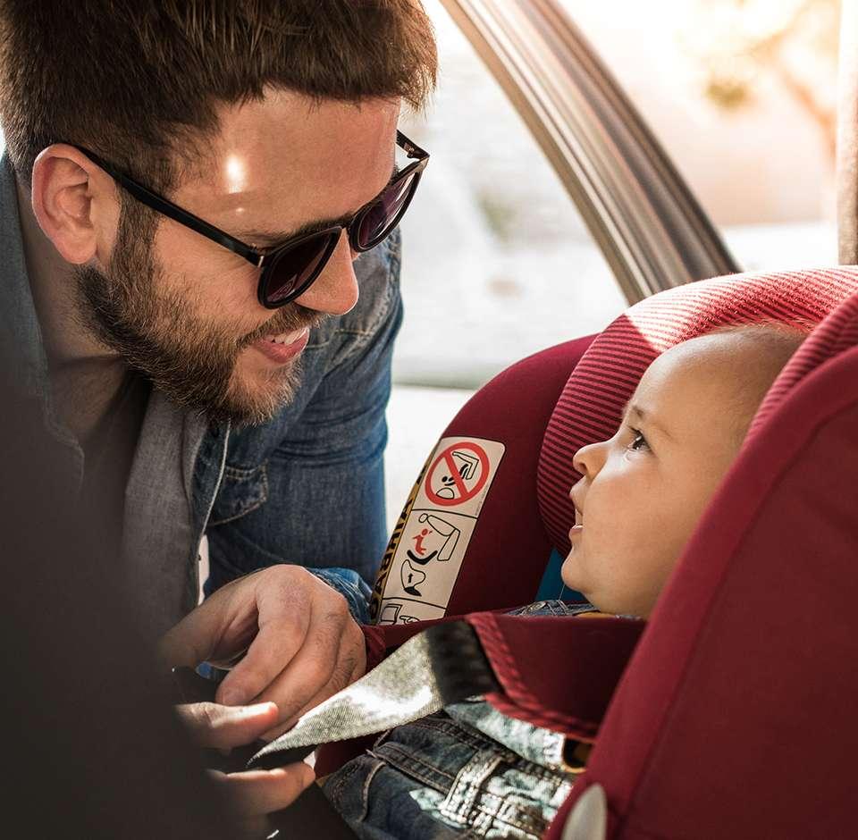 Un homme installe son bébé dans la voiture