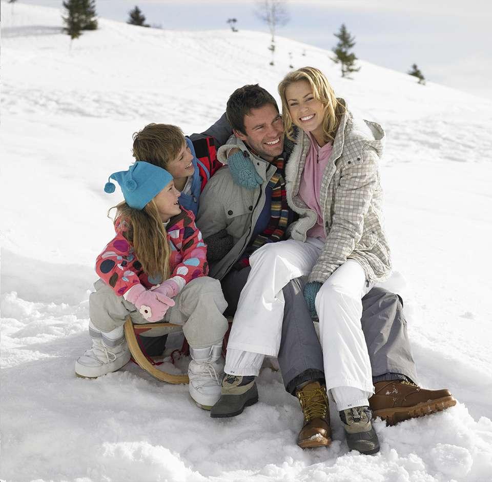 Famille heureuse assises sur une luge dans la neige
