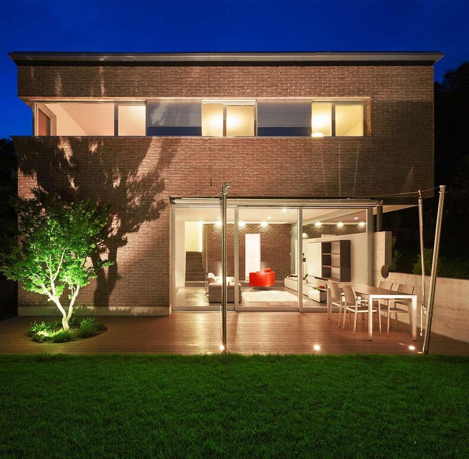 Maison de standing éclairée la nuit côté jardin