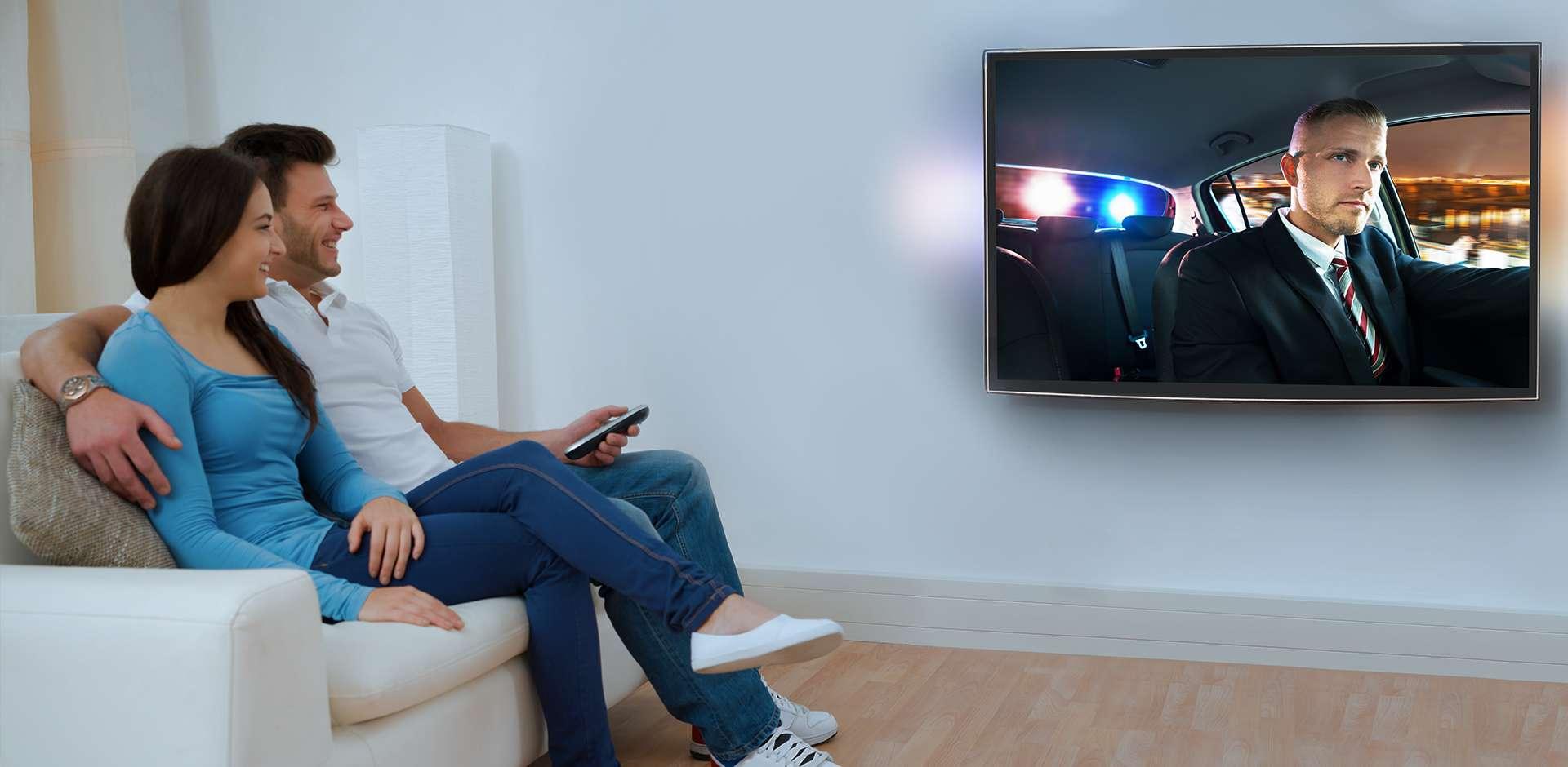 Un couple regarde la télé dans une ambiance tamisée