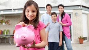 Une petite fille tenant un cochon tireolire rose