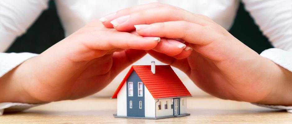 Deux mains protectrices au-dessus d'une maquette de maison